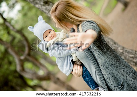 Beautiful american girl with a Chinese baby are happy in park