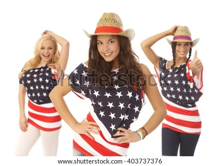 Beautiful American girls posing in American flag t-shirt and straw hat, smiling happy over white background.
