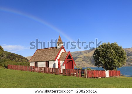 Beautiful ancient Maori church under the rainbow in Akaroa, New Zealand - stock photo