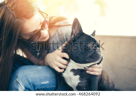 Beautiful and adorable French bulldog sitting with her owner girl in cafe bar. Hot summer day. Strong backlight.