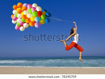 Beautiful and athletic girl with colorful balloons jumping on the beach - stock photo
