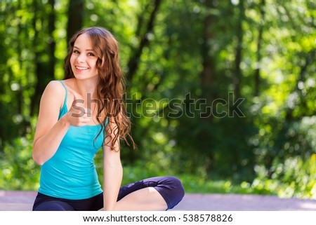 Beautiful and athletic girl with sport clothes looking at the camera and thumbs up.