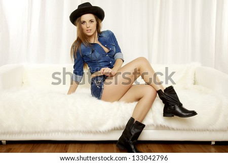 Beautiful and attractive female blonde woman posing in blue jeans short and jacket on the white sofa