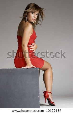 beautiful and attractive lady in red dress on grey background