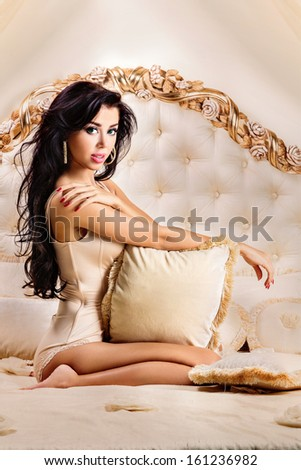 Beautiful and attractive young adult female brunette sensuality woman posing on bed in exclusive apartment - stock photo
