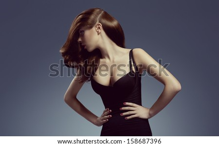 beautiful and attractive young brunette lady in elegant black dress and shining hair. Hair style  - stock photo