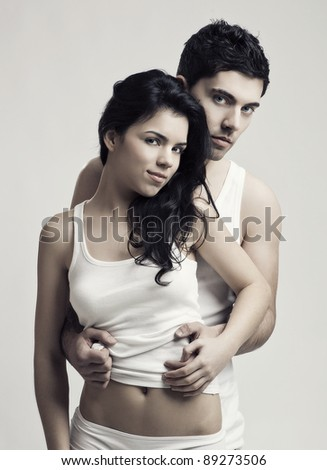 Beautiful and attractive young couple in underwear standing over a white background - stock photo