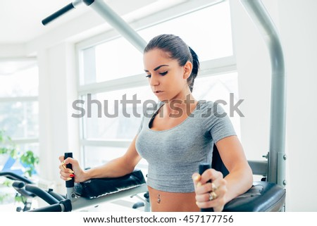 Beautiful and attractive young woman doing exercises at fitness gym.