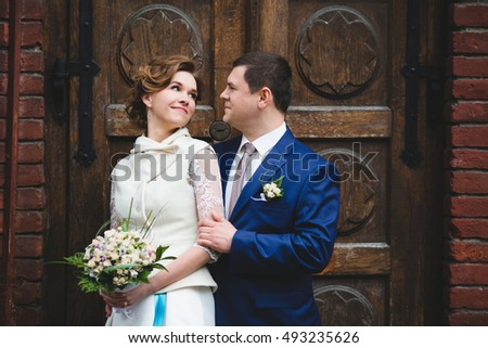 Beautiful and charming couple standing near the door