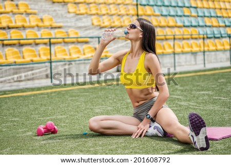 Beautiful and charming girl in a sports suit fitness drinks water. Girl sitting on the football field - stock photo