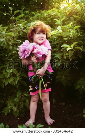 Beautiful and cheerful girl holding a bouquet of peonies - stock photo