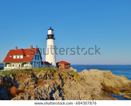 Beautiful and colorful scene along the Atlantic Ocean coast in Maine with the Portland Head Lighthouse sitting on the rocky ocean side with the sea in the background under a bright blue sky.