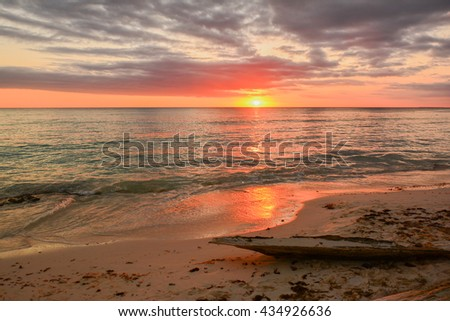 beautiful and colorful sunset of the Caribbean in the Dominican Republic in the small town Tropical Bayahibe with white sand and coconut palms