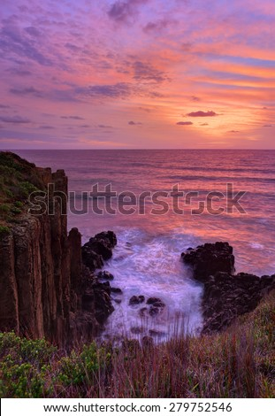 Beautiful and colourful sunrise over the ocean with volcanic sea cliffs rising up at Minnamurra. - stock photo