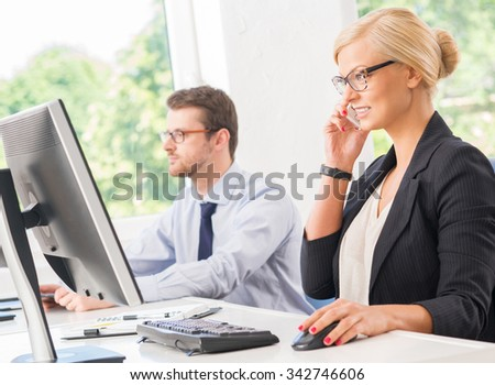 Beautiful and confident female ceo having a business conversation over smartphone. - stock photo