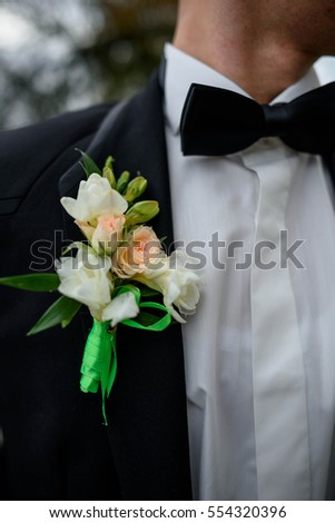 Beautiful and delicate boutonniere on blue jacket of the groom