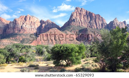 Beautiful and dramatic scenery in Zion National Park includes colorful sandstone and shale mountains, rock formations, and lush green foliage - stock photo
