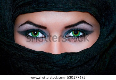 Beautiful and elegant close up of a young girl's green eyes with dark white make up, and face covered by a black scarf.