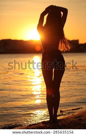 Beautiful and fashion young woman in boho fashion style outfit posing at beach. Slim girl standing and looking to a sea. Female silhouette in the sunset on the beach. Vitality healthy living concept - stock photo