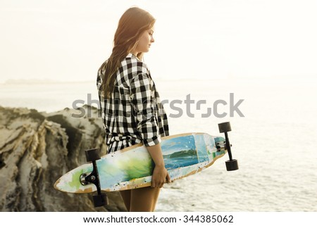 Beautiful and fashion young woman posing at the sunset with a skateboard  - stock photo