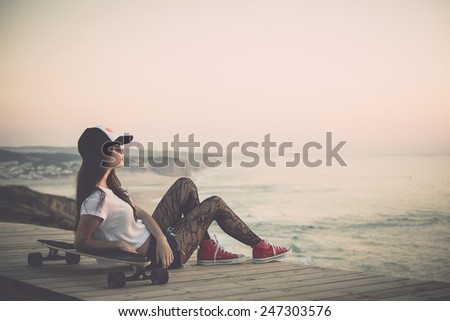 Beautiful and fashion young woman posing with a skateboard - stock photo