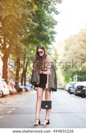 beautiful and fashionable young woman posing on the street. fashionable street style, warm grade.