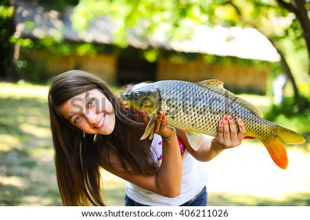 Beautiful and funny fisher woman smiling and holding big fish catch on nature background. Happy young fisherwomen, teenage girl rest outdoors and enjoy vacation in summer with fish catch. - stock photo