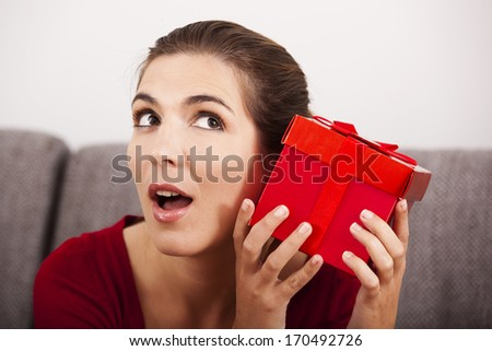 Beautiful and happy woman trying to guess what is inside the christmas present - stock photo