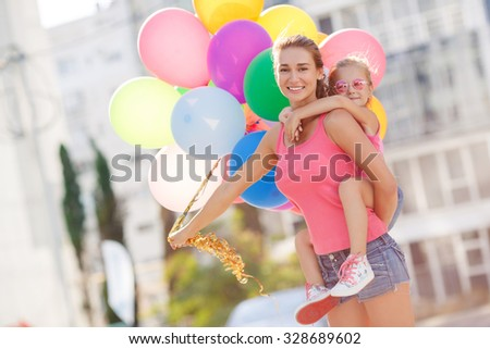 Beautiful and happy young mother giving piggyback ride to her daughter. Both smiling and looking into the camera. Summer city in background. Mother holding daughter outdoors smiling - stock photo