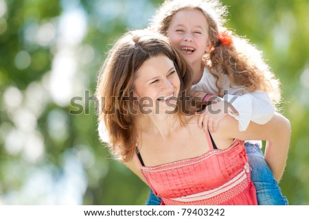Beautiful and happy young mother giving piggyback ride to her laughing daughter - stock photo