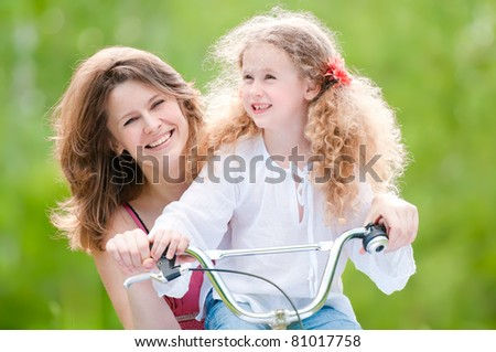 Beautiful and happy young mother on bicycle with her daughter. Both smiling, summer park in background.