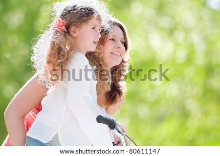 Beautiful and happy young mother teaching her daughter to ride a bicycle. Both smiling, summer park in background. - stock photo