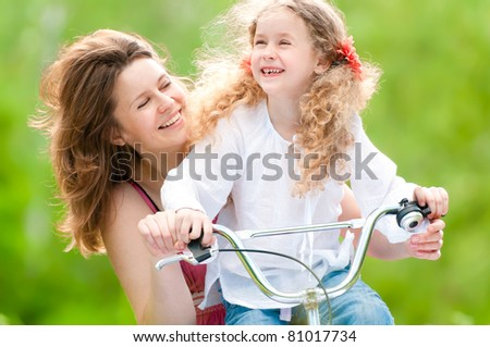 Beautiful and happy young on bicycle with her daughter. Both smiling, summer park in background. - stock photo