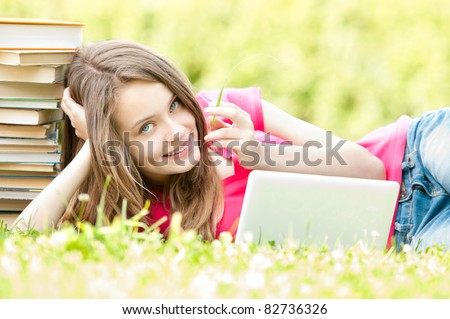 beautiful and happy young student girl lying on grass with laptop computer, smiling and looking into the camera. Pile of books near her head. Summer or spring green park in background - stock photo