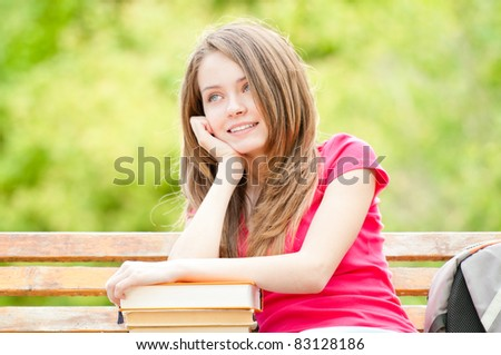 beautiful and happy young student girl sitting on bench, her hands on pile of books, looking away from the camera, smiling and daydreaming. Summer or spring green park in background - stock photo