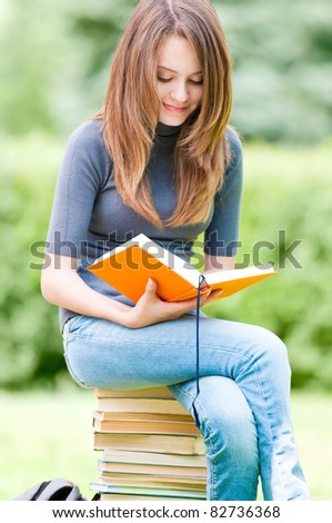 beautiful and happy young student girl sitting on pile of books, holding book in her hands, smiling and reading. Summer or spring green park in background - stock photo