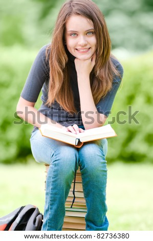 beautiful and happy young student girl sitting on pile of books, holding book in her hands, smiling and looking into the camera. Summer or spring green park in background - stock photo