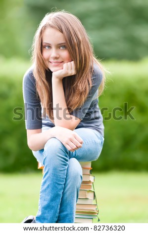 beautiful and happy young student girl sitting on pile of books, smiling and looking into the camera. Summer or spring green park in background - stock photo