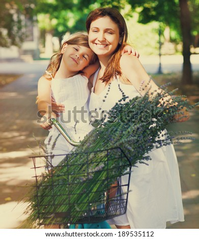 Beautiful and happy young woman on bicycle with her daughter. Both smiling, summer park in background - stock photo