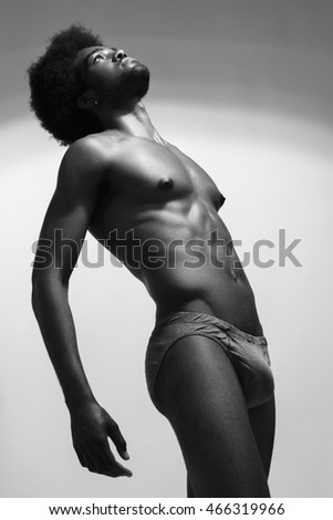 Beautiful and health athletic muscular young man. Black-white photo.