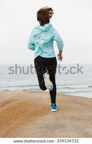 Beautiful and healthy woman running on the beach  - stock photo