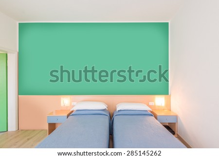 Beautiful and modern home and hotel bedroom interior design. Green walls, blue blankets and hardwood floor.