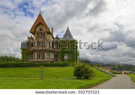 Beautiful and old victorian house in a little hill surrounded with green grass and a dirt track - stock photo
