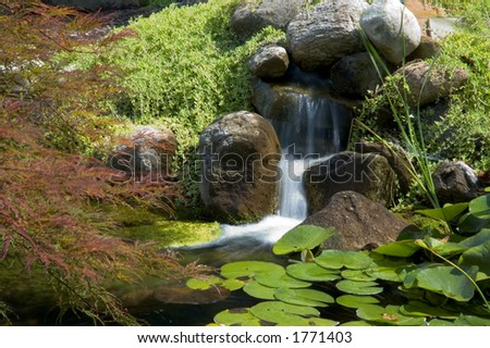Beautiful and peaceful Japanese water garden. Complete with a small waterfall. - stock photo