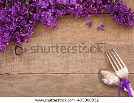 Beautiful and scented, Purple Lavender Flowers place Setting with fork and spoon on Rustic Wood Background with room or space in center for copy, text, your words.  Horizontal card with top down view