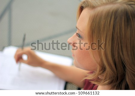 Beautiful and Serious Business Woman Thinking While Writing - stock photo