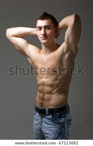 Beautiful and sexy muscular man posing on a gray background