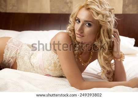 Beautiful and sexy sensuality young adult pretty blonde woman wearing elegance fashionable lingerie corset on the bed in luxury style apartment