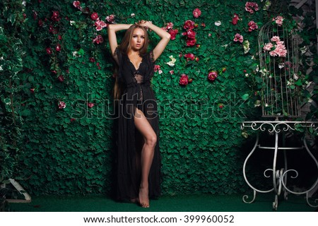 Beautiful and sexy woman in black peignoir with long hair in a green wall of flowers and leaves