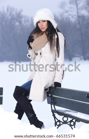 Beautiful and sexy woman sitting on bench in snowy outdoors - stock photo